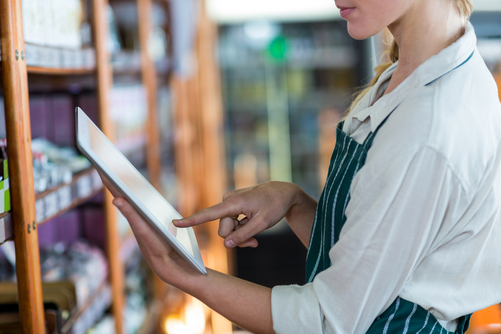 Mid-section of female staff using digital tablet in super market-1