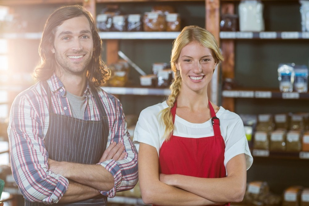 Portrait of smiling staffs standing with arms crossed in supermarket